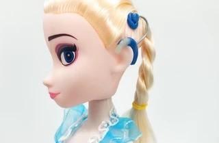 Foto da cabeça da boneca Elsa, da animação Frozen, que um implante coclear.